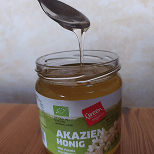 Flüssiger Akazien-Honig der vom Löffel in ein Honigglas tropft